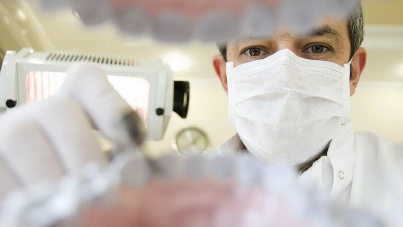 Zahnarzt mit Mundschutz bei Zahnuntersuchung
