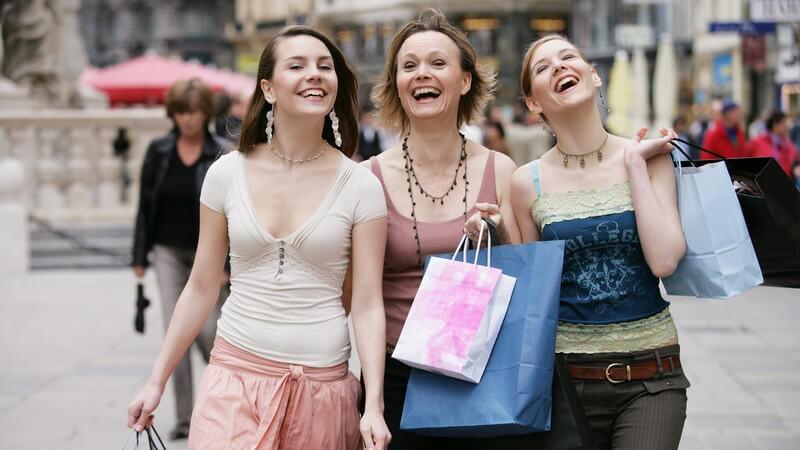 Drei lachende Freundinnen mit Einkaufstaschen beim Shoppen