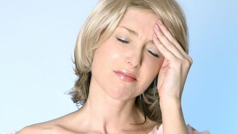 Blonde Frau mit Kopfschmerzen vor hellblauem Hintergrung fasst sich mit geschlossenen Augen an die Stirn