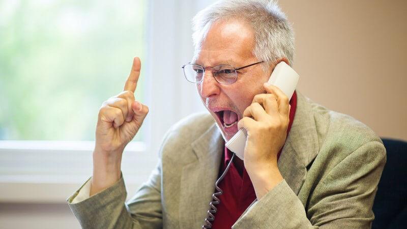 Mann in hellgrauem Sacko und mit Brille sitzt am Telefon und schreit hinein, erhobener Zeigefinger