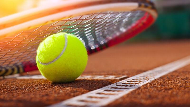 Tennisball liegt unter einem Schläger auf rotem Sandplatz