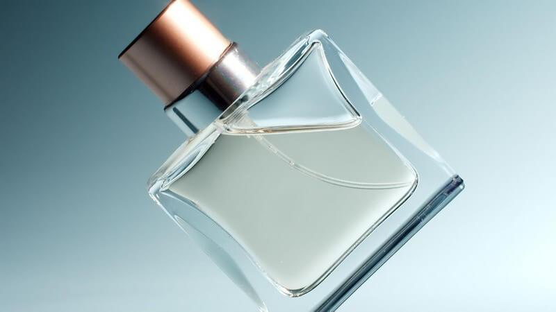 Parfümflasche gekippt steht auf Ecke, blauer Hintergrund