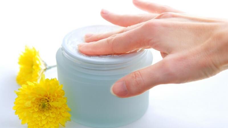 Rechte Hand in Cremedose, daneben gelbe Blüten