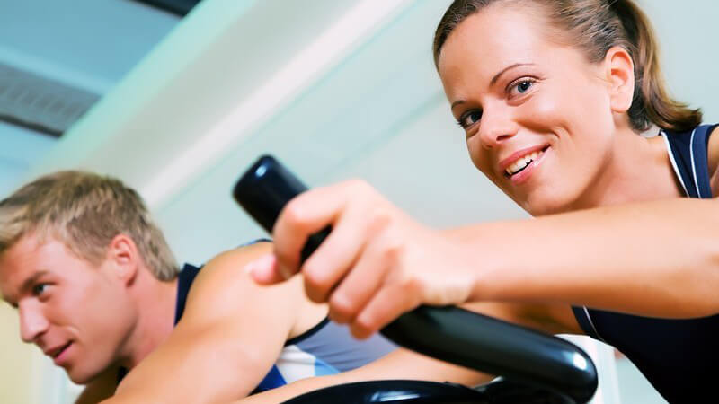 Junge Frau auf Spinningrad im Vordergrund, nur der Lenker sichtbar, in Fitnessstudio, junger Mann im Hintergrund