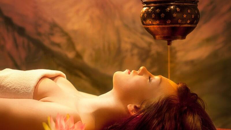 Junge Frau mit Handtuch über der Brust liegt in einer Art Gewölbe neben einer Lotusblume und bekommt einen Stirnölguss