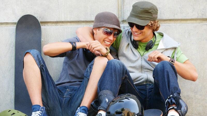 Zwei Freunde mit Skateboars sitzen an Mauer und lachen zusammen