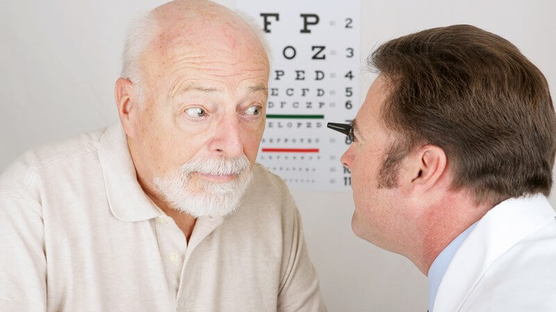 Augenarzt untersucht Auge eines älteren Mannes
