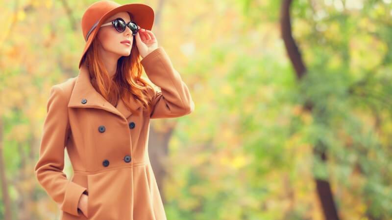 Herbst - Frau mit Mantel, Hut und Sonnenbrille macht Spaziergang im Park