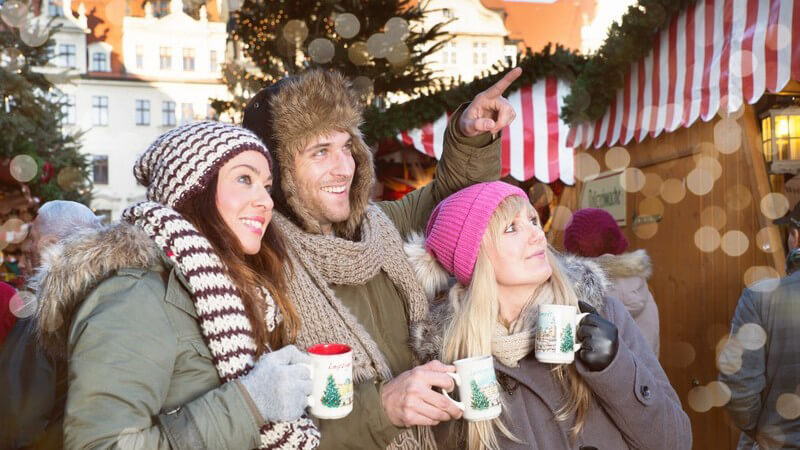 Drei Freunde mit Mütze, Schal und Glühweintasse auf einem Weihnachtsmarkt