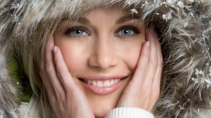 Gesichtsportrait junge Frau mit Pelzkapuze, Hände am Gesicht, Schnee auf Pelz