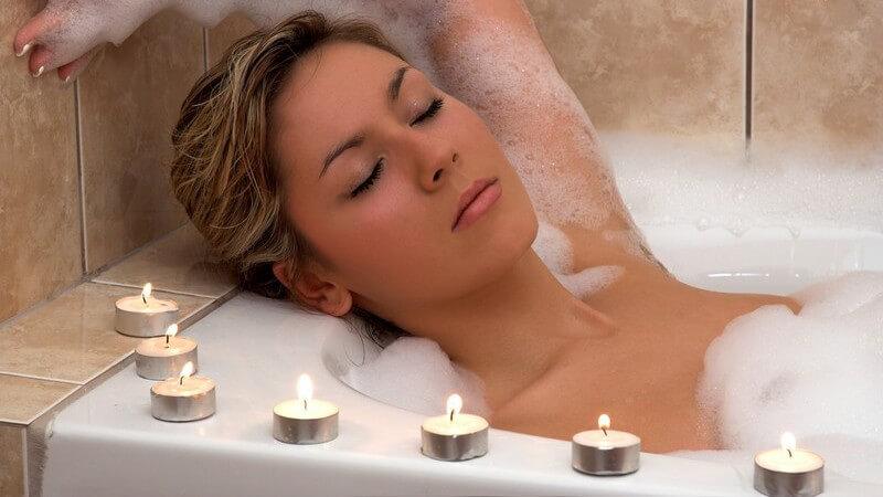 Junge Frau liegt im Schaumbad in Badewanne mit Teelichtern auf dem Rand, geschlossene Augen, terrakotta-farben