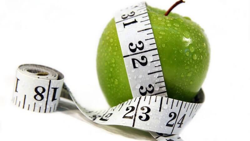 Frischer grüner Apfel, gerade gewaschen, Maßband darum gelegt