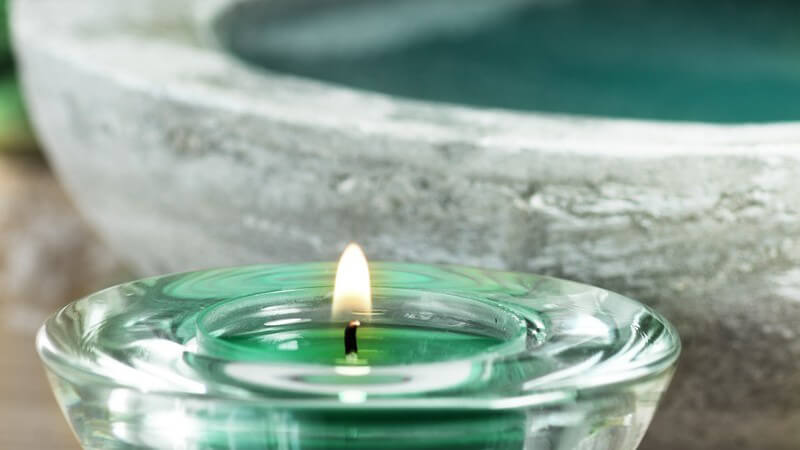 Brennendes grünes Teelicht (Duftkerze) in flachem Glaskerzenhalter vor grauem Naturstein-Waschbecken