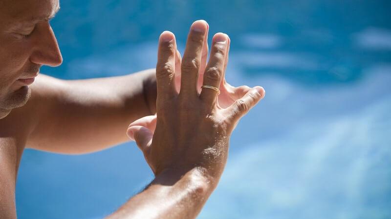 Mann legt Fingerspitzen der Hände aneinander und meditiert mit geschlossenen Augen, mit blauem Hintergrund