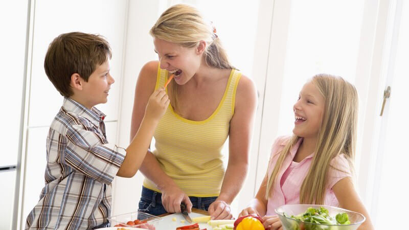 Mutter mit ihren beiden Kindern in Küche beim Gemüseschneiden