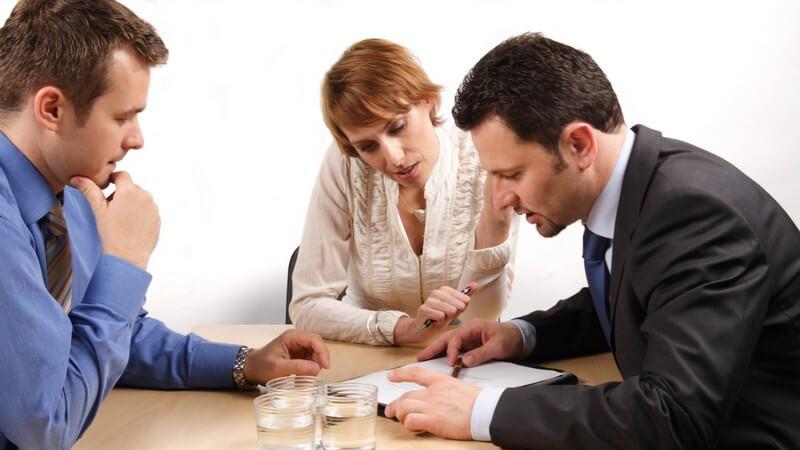 Drei Geschäftsleute sitzen am Tisch und besprechen einen Vertrag