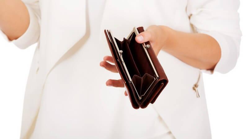 Frau in hellem Blazer hält eine leere Geldbörse vor weißem Hintergrund