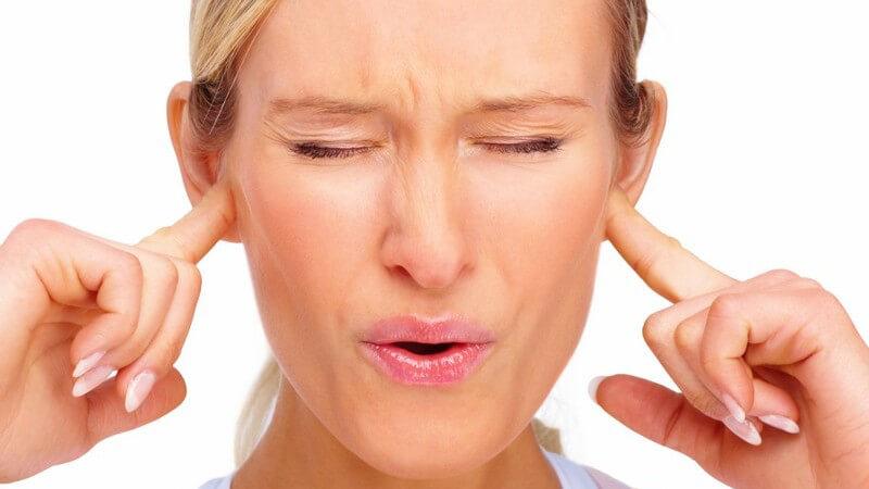 Frau hält sich genervt die Ohren zu