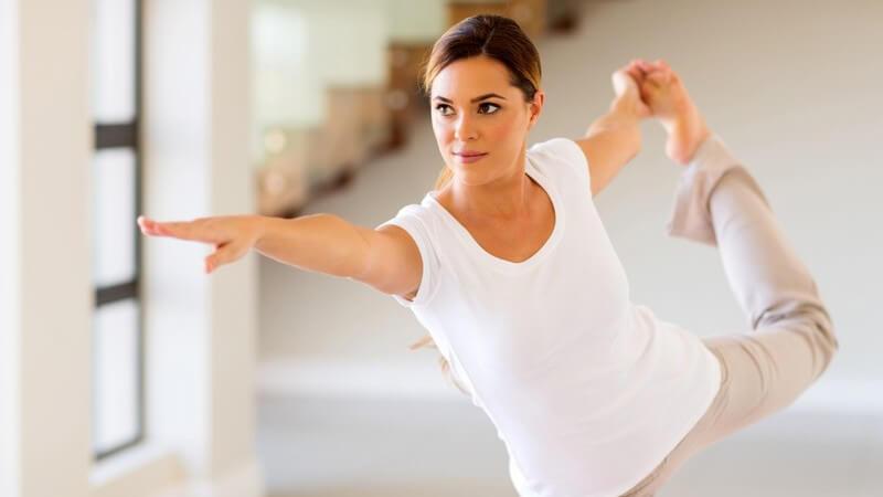 Frau in Sportklamotten bei einer Yoga-Übung, eine Hand hält ein Bein und ein Arm ist nach vorne ausgestreckt