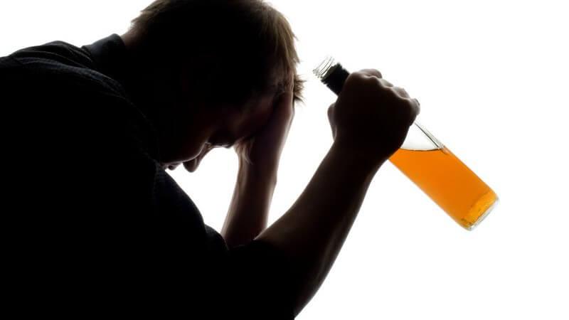 Seitenansicht Mann hat Kopf in Hand gestützt, in anderer Hand Flasche mit Alkohol
