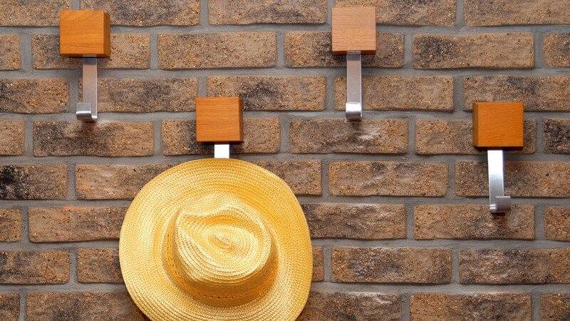 Garderobe an Mauerwand, Hut hängt am Haken
