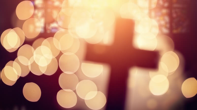Unscharfes Aufnahme in einer Kirche mit Kreuz und vielen Lichtpunkten im Vordergrund