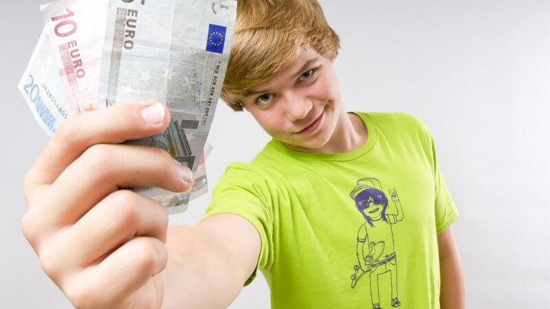 Jugendlicher in grünem Shirt hält drei Geldscheine in die Kamera