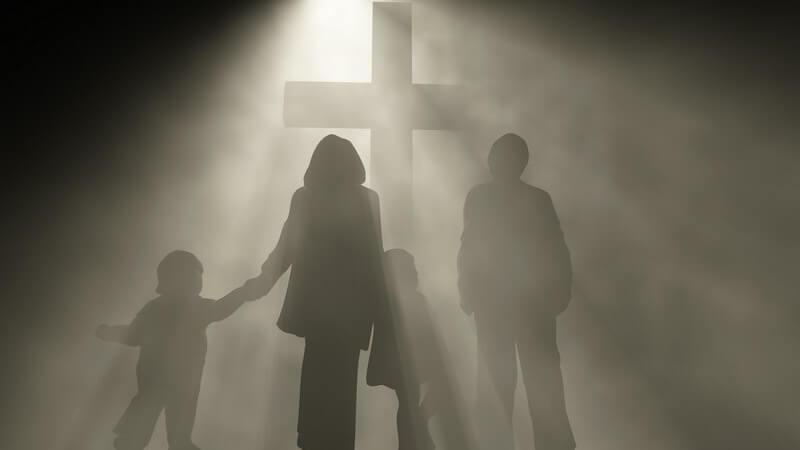Eltern mit Kindern vor großem Kreuz, Grab, Friedhof