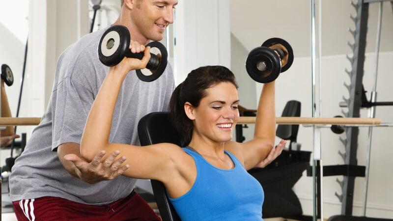 Junger Mann unterstützt junge Frau in Fitnessstudio beim Hanteltraining auf Trainingsbank