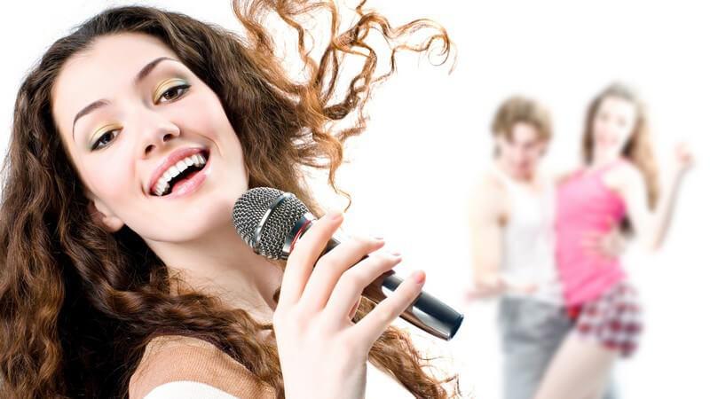 Junge, dunkelhaarige Frau singt mit Mikrofon, im Hintergrund ein tanzendes Paar