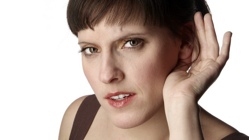 Junge Frau hält sich linke Hand hinters Ohr zum Hören