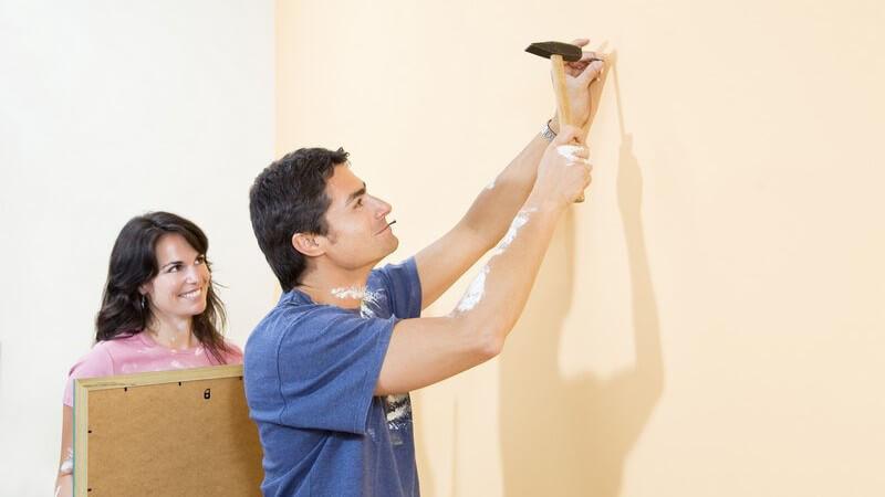 Paar beim Renovieren, Mann schlägt Nagel mit Hammer in Wand, Frau hält Bild zum Aufhängen