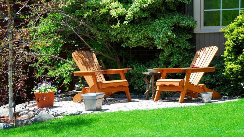 Zwei Gartenstühle auf kleiner Terrasse an Rasen