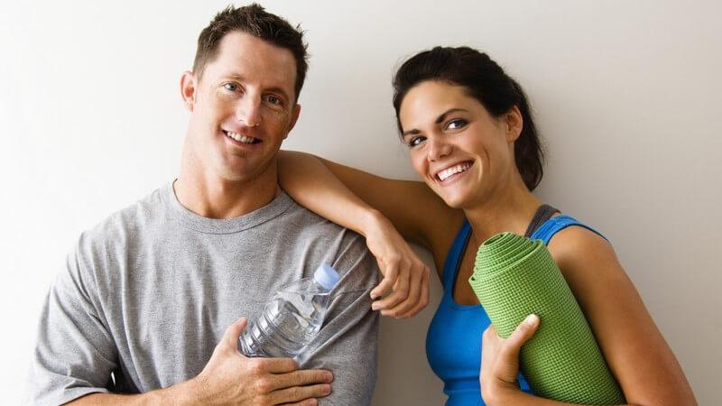 Junges Paar an Wand gelehnt, Gymnastikmatte und Wasserflasche für Sport in Händen