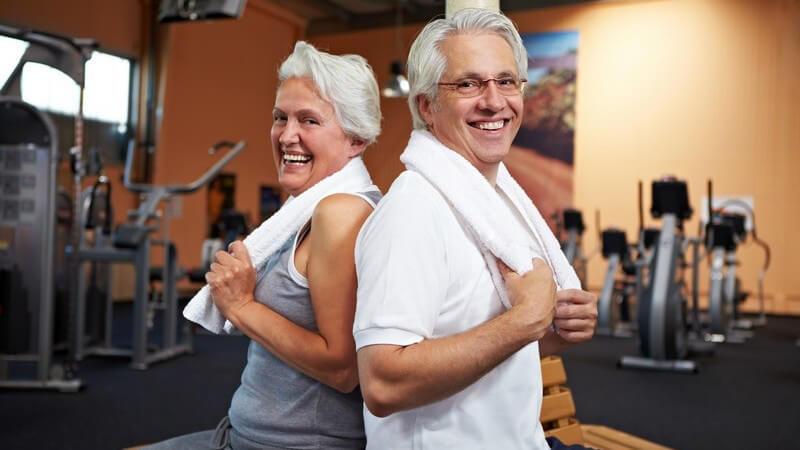 Älteres Paar mit weißen Handtüchern über den Schultern im Fitness-Studio