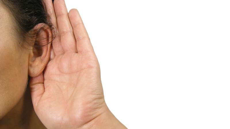 Ausschnitt Frauengesicht, Frau hält Hand hinter linkes Ohr, weißer Hintergrund