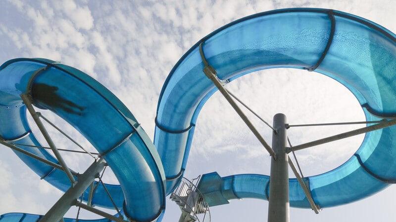 Große, blaue Wasserrutsche unter wolkigem Himmel, links die Silhouette eines rutschenden Badegastes