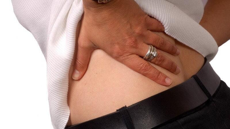 Nahaufnahme Frau legt Hand auf unteren Rücken, Rückenschmerzen