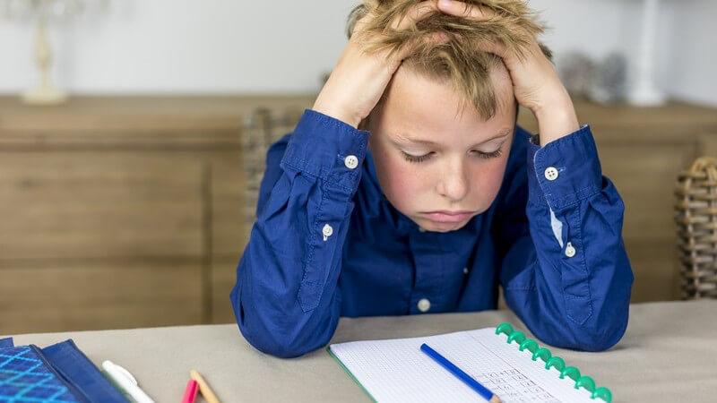 Junge in blauem Hemd sitzt verzweifelt an den Hausaufgaben, die Hände im Haar
