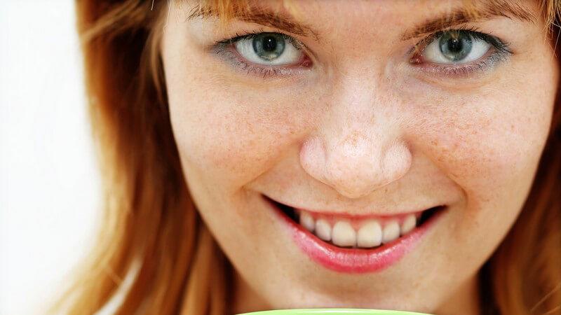 Rothaarige Frau mit Sommersprossen hält Kaffee und lächelt in die Kamera
