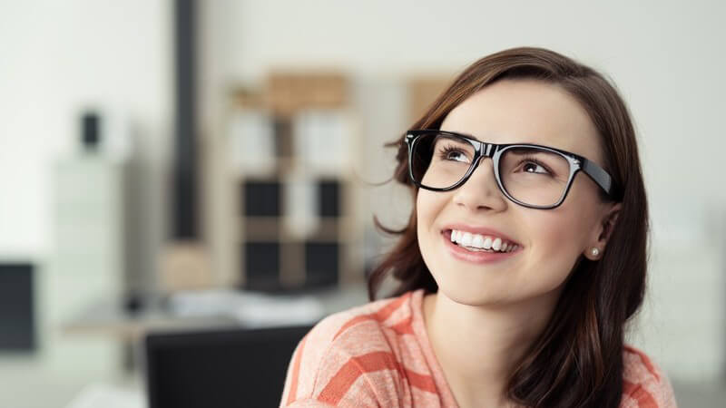 Junge lächelnde Frau mit braunen Haaren und großer Hornbrille blickt zufrieden nach oben