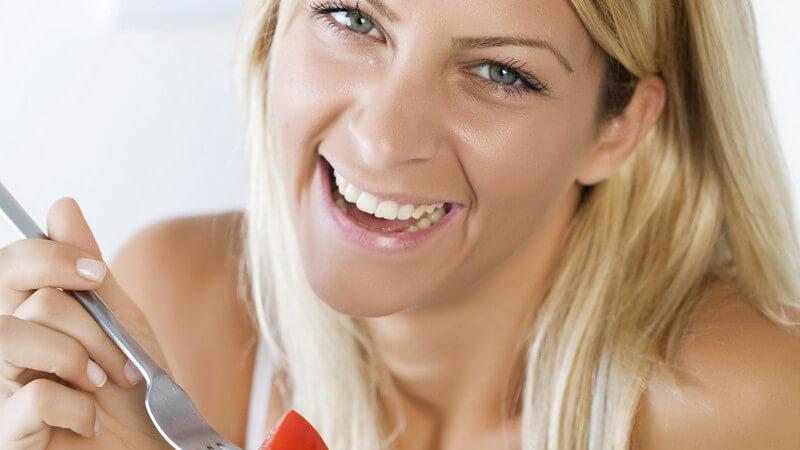 Junge blonde Frau lacht in Kamera, hält Salatteller in einer Hand und Gabel mit Tomate in der anderen