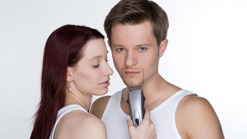 Paar Arm in Arm, sie hält Rasierer an seinen Hals