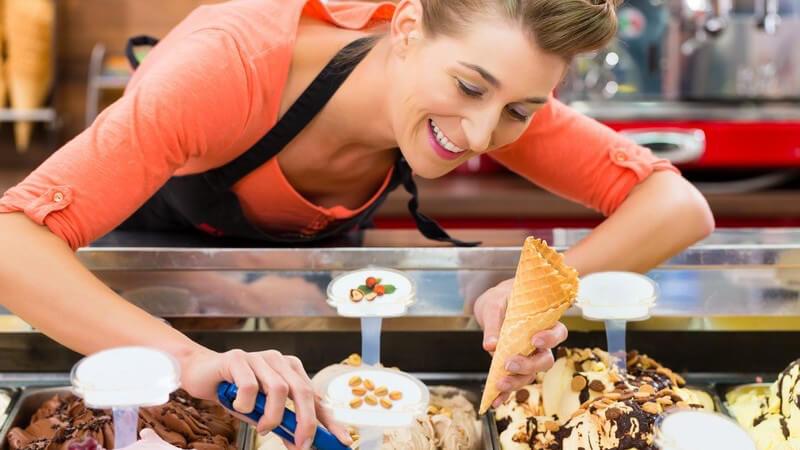 Eisverkäuferin mit Schürze füllt in einer Eisdiele ein Hörnchen mit Eiskugeln