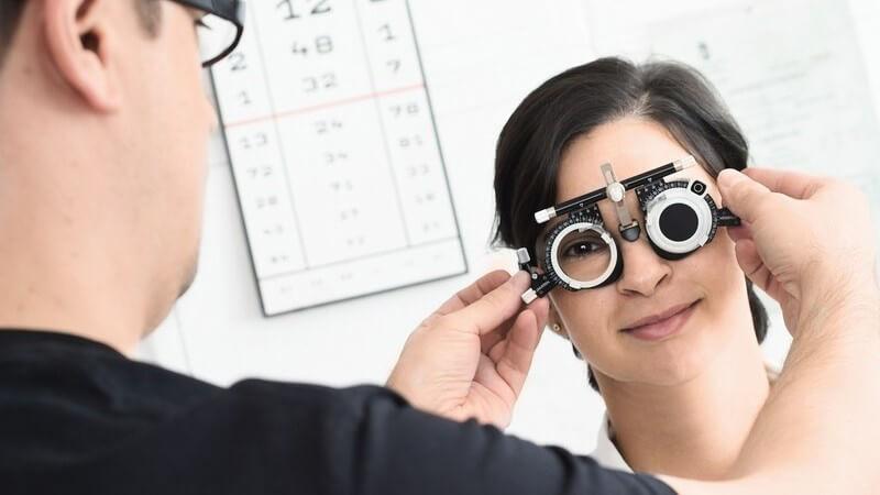 Patientin beim Augenarzt, der ihr eine Messbrille aufsetzt
