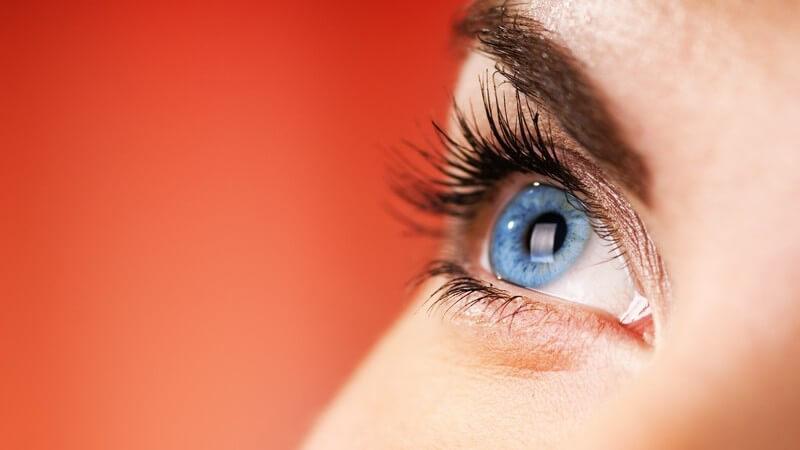 Auge einer jungen Frau vor einem rotem Hintergrund