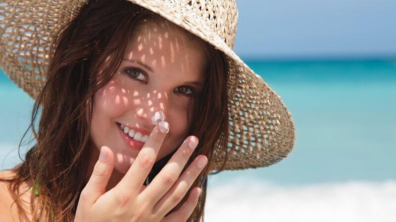Junge Frau mit Sonnenhut am Strand, Sonnencreme auf Nase