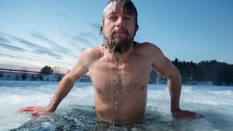 Mann mit Vollbart badet in einem Loch in der Eisdecke eines zugefrorenen Sees