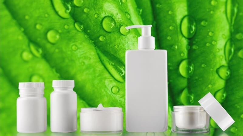 Fünf verschiedene weiße Kosmetikprodukte vor einem grünen Blatt voller Wassertropfen