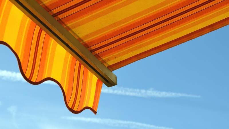 Orange-gelbe Markise unter blauem Himmel